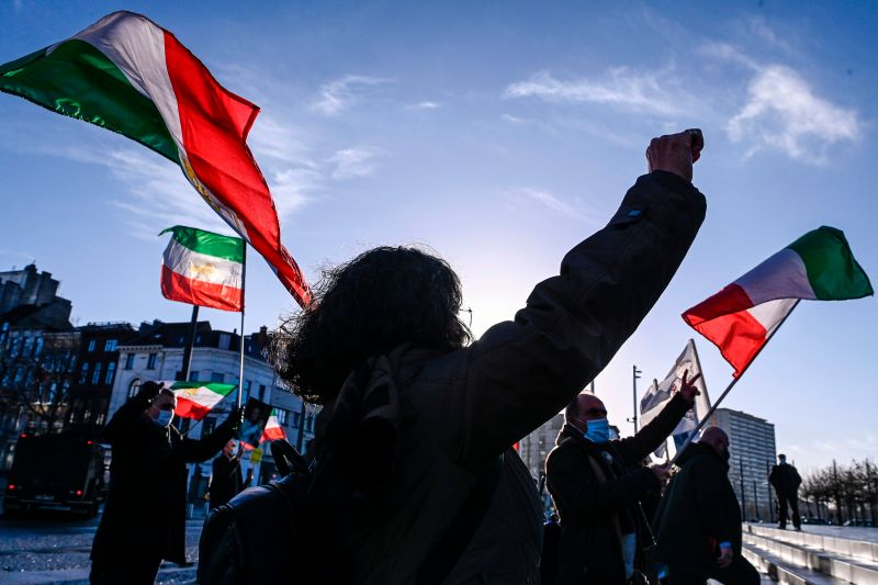 People gesture and wave former flags of Iran as they protest outside the Antwerp criminal court during the trial of four persons including an Iranian diplomate and Belgian-Iranian couple in Antwerp, on February 4, 2021.