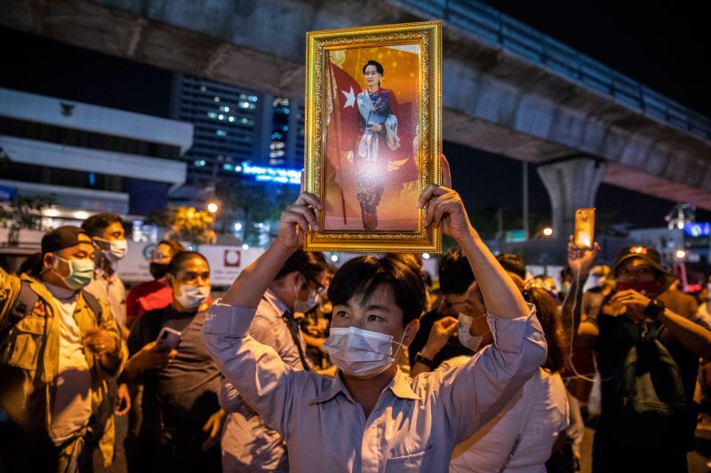 An anti-coup protester holds up a portrait of Aung San Suu Kyi in front of the Myanmar embassy on Feb. 4 in Bangkok.