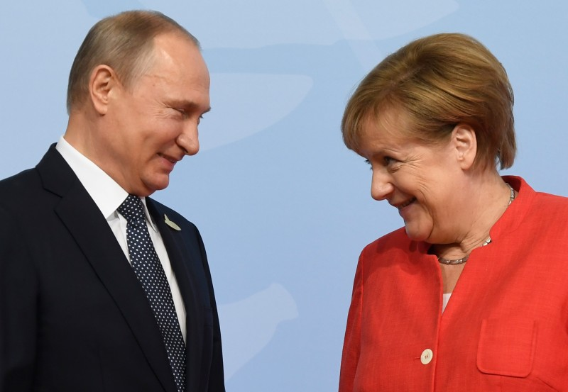 German Chancellor Angela Merkel welcomes Russia's President Vladimir Putin as he arrives to attend the G20 summit in Hamburg, northern Germany, on July 7, 2017.