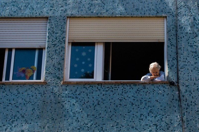 An elderly woman looks out from her window in Barcelona, Spain, on April 26, 2020.