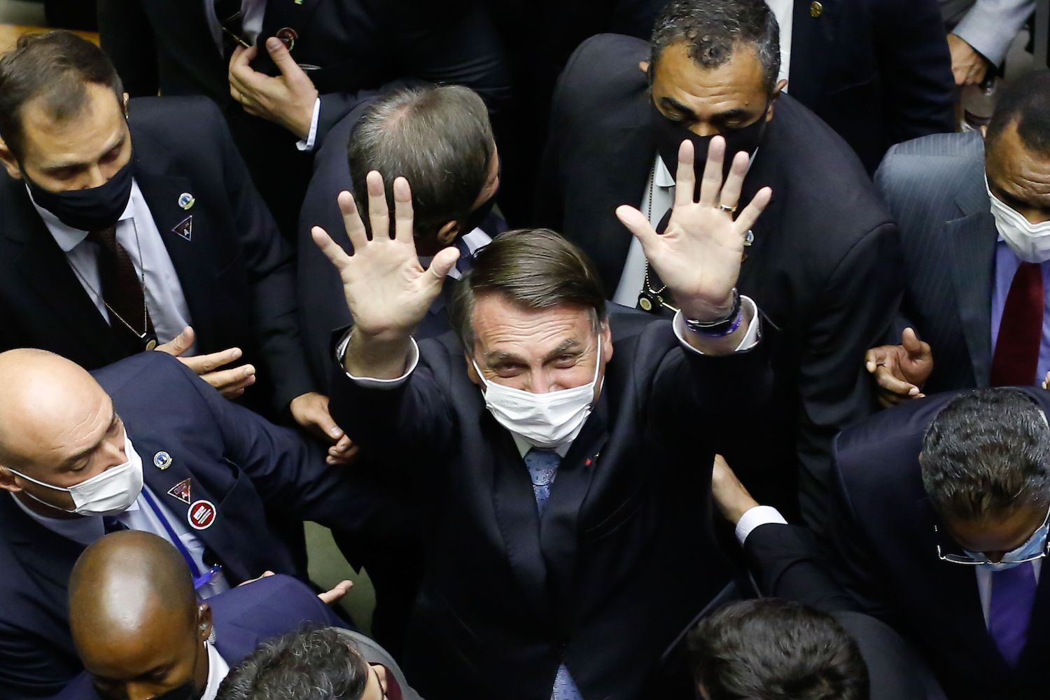 Brazilian President Jair Bolsonaro waves as he leaves the National Congress after a plenary session of the Chamber of Deputies, in Brasilia, on Feb. 3