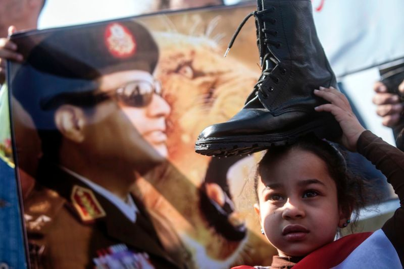 A supporter of Abdel Fattah al-Sisi, then Egypt's army chief, holds a military boot on her head in a sign of support for military rule in Cairo on Jan. 28, 2014.
