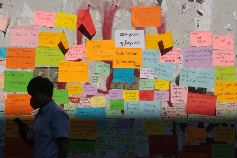 A man walks past a wall of messages of support for the ongoing protests against the military coup in Yangon on Feb. 11.