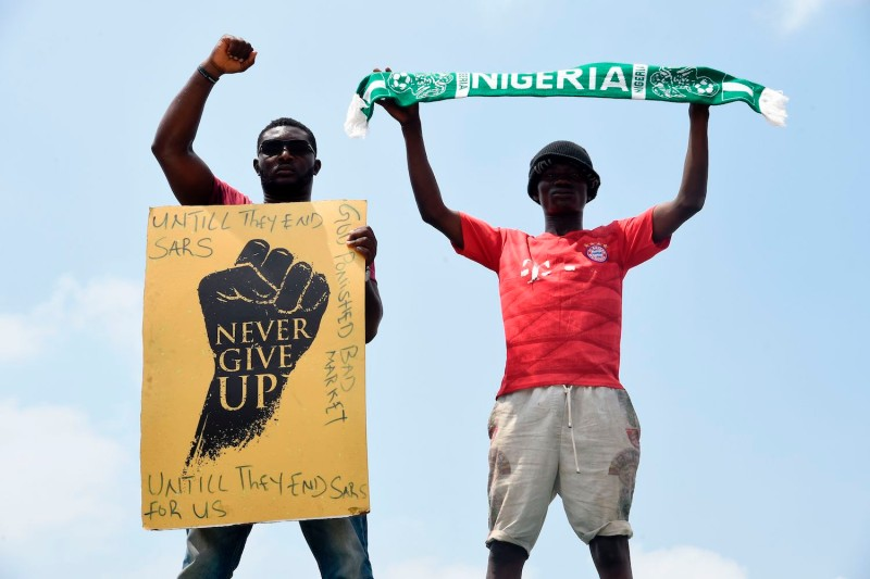 "A protester gestures while holding placard that says ""Never Give Up"" as another holds up a scarf with the colors of the Nigerian national flag during a demonstration to protest against police brutality in Magboro, Nigeria, on Oct. 20, 2020."