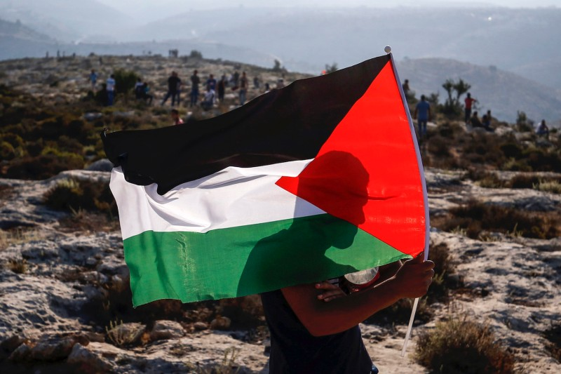 A Palestinian protester waves a Palestinian flag during a demonstration in the village of Ras Karkar in the occupied West Bank, on Sept. 4, 2018.