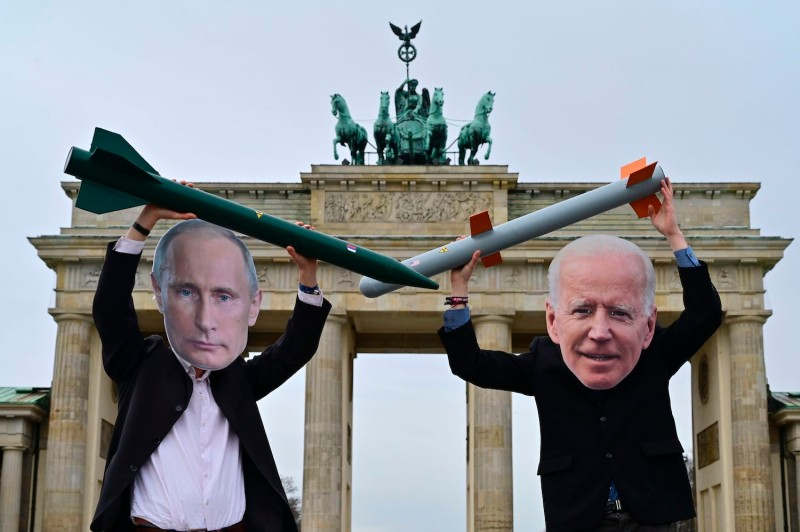 Peace activists wearing masks of Russian President Vladimir Putin and U.S. President Joe Biden pose with mock nuclear missiles in front of the Brandenburg Gate in Berlin on Jan. 29.