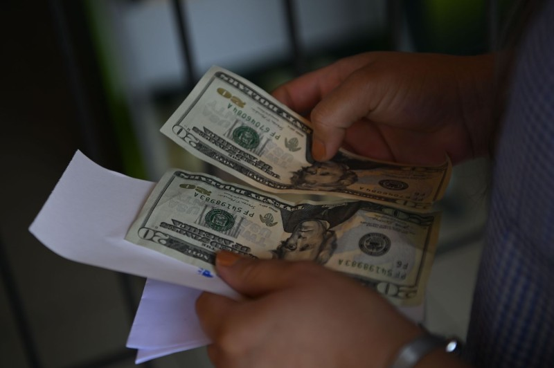 A woman counts money outside a U.S. remittance collection agency in San Isidro, San Salvador, on June 10, 2020.