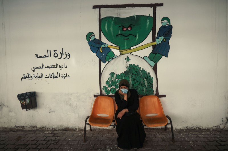 A patient sits on a bench in front of a coronavirus-inspired mural in Gaza City, Gaza Strip, on Feb. 1.