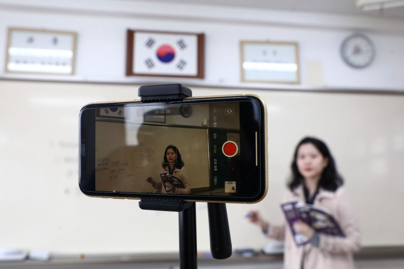 A teacher prepares a lesson with a cellphone on the first day of online classes in an empty classroom in Seoul, on April 9, 2020.