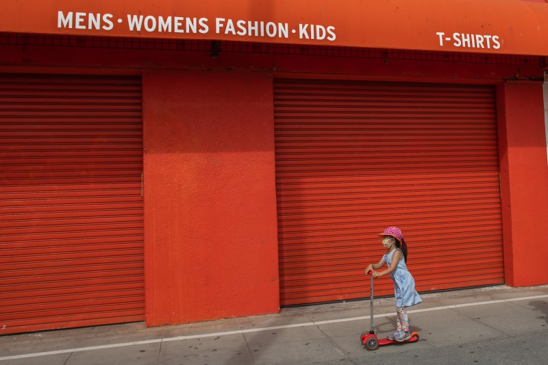 A girl wearing a mask, rides a scooter by the closed stores of the Boardwalk in Venice, California on Apr. 26, 2020.