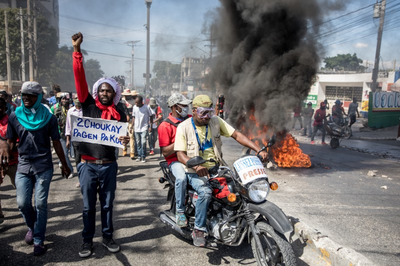 Protesters walk past a burning barricade as opponents of Haitian President Jovenel Moïse demonstrate on Jan. 15 in Port-au-Prince to demand his departure from power.