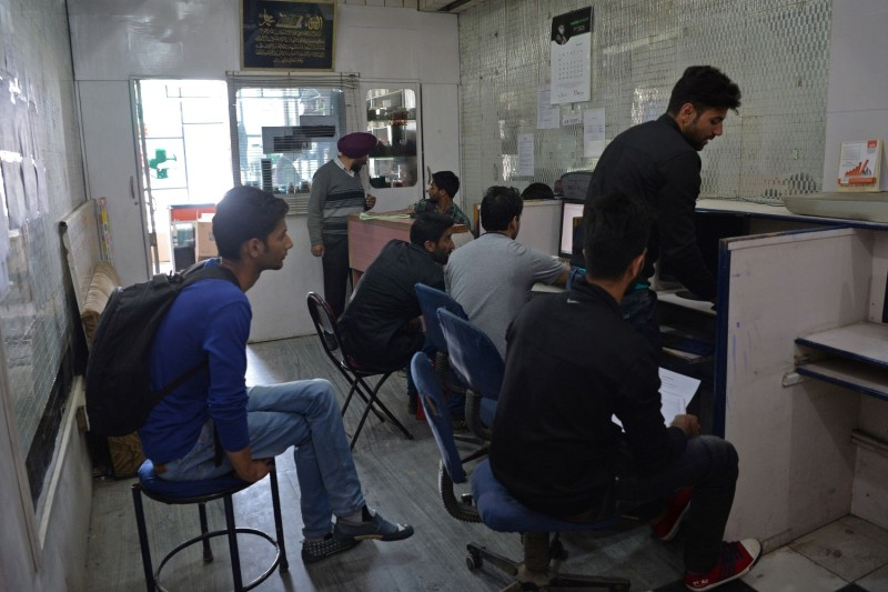 Indian Kashmiri men sit in an internet cafe in Srinagar, India, on April 27, 2017.