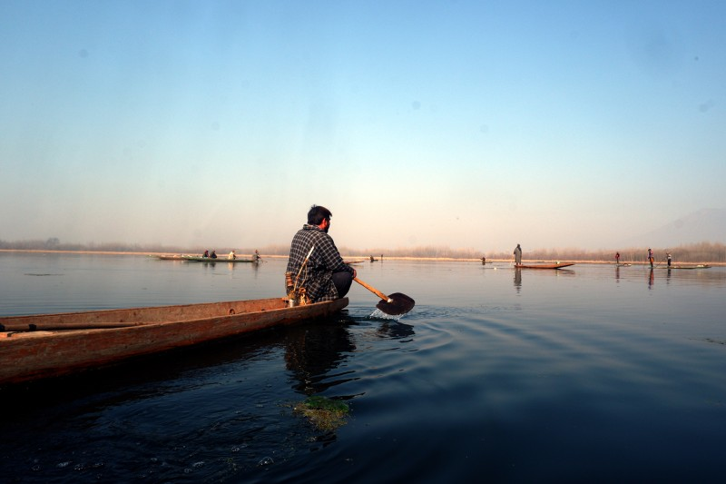 After waiting for hours, Nazir Ahmad Kondoo rows his boat toward other fishermen on Anchar Lake in Srinagar, Jammu and Kashmir, on Feb. 16.