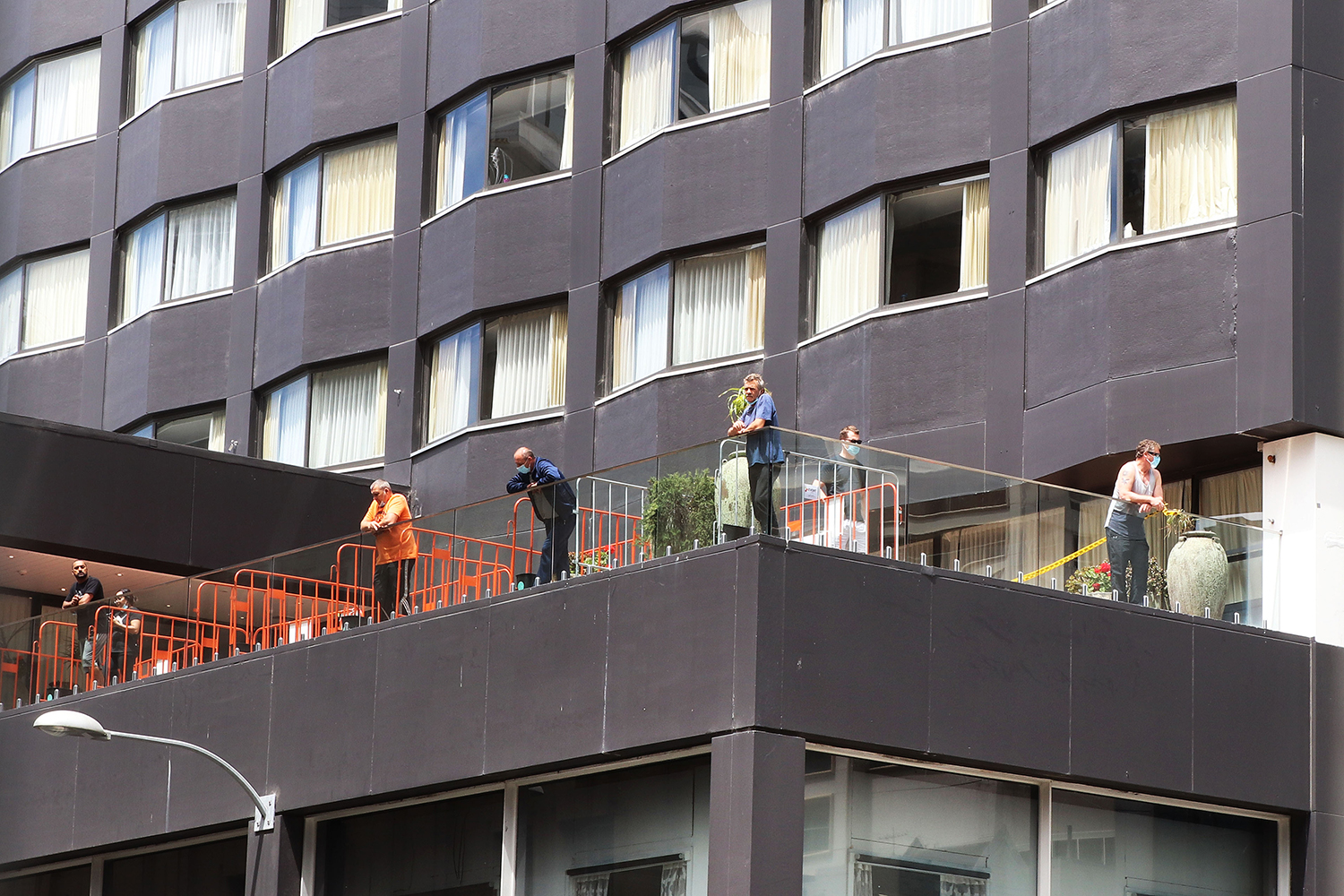 Quarantined people take in the view from a rooftop terrace at the Grand Mercure Hotel, used to isolate returning New Zealanders during coronavirus quarantine protocols, in Auckland on Oct. 29, 2020.