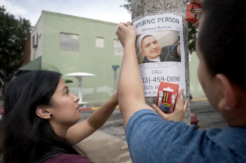 Omar Roman and Michelle Chinos hang a poster in their search for family member Homero Roman Gómez in Brooks County, Texas.