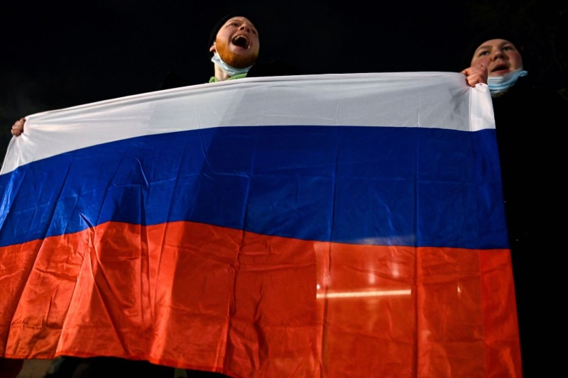 Men holding a Russian flag protest against a Moscow court's decision to sentence the Russian opposition leader Alexey Navalny to almost three years' imprisonment in Moscow on Feb. 2.