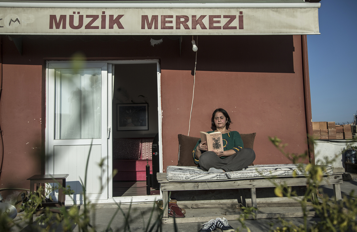 Guzel reads a book on the balcony of her apartment on the rooftop of an old rusty building in Mersin on Nov. 23, 2020.