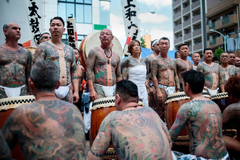 Participants pose to show their traditional Japanese tattoos (Irezumi), associated with the yakuza, during the annual Sanja Matsuri festival in the Asakusa district of Tokyo on May 20, 2018.