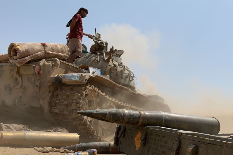 A fighter in Yemen stands atop a tank.
