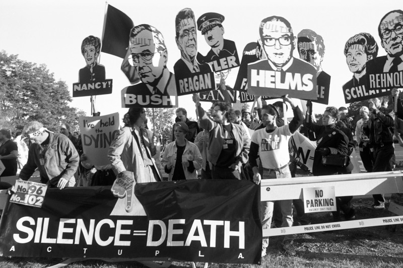 "Members of AIDS activist group ACT UP hold up signs of George W. Bush, Ronald Reagan, Nancy Reagan, and Jesse Helms along with a banner stating ""Silence Equals Death"" as they protest at the headquarters of the Food and Drug Administration in Rockville, Maryland, on Oct. 11, 1988."