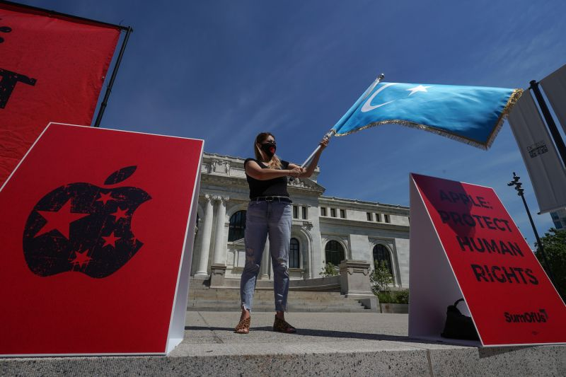 Activist Irade Kashgary waves a flag of the Uighur region as she takes part in a protest outside of the Apple Store on K Street on July 30, 2020 in Washington.