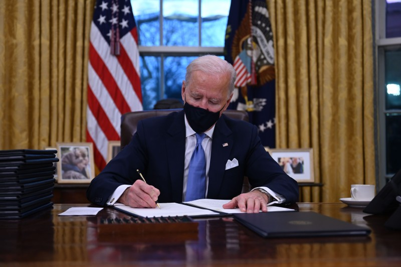 U.S. President Joe Biden signs executive orders, including a decision to rejoin the Paris Agreement, at the White House in Washington on Jan. 20.