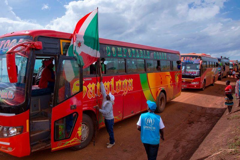 A man hangs a Burundian flag on the lead bus transporting repatriated refugees arriving at the Gisuru border crossing on Oct. 3, 2019 in Ruyigi, Burundi.