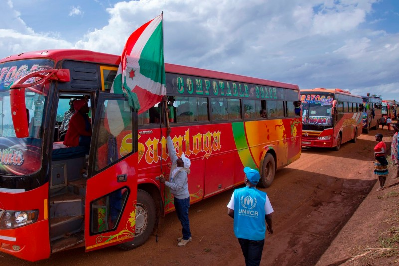 A man hangs a Burundian flag on the lead bus transporting repatriated refugees arriving at the Gisuru border crossing on Oct. 3, 2019 in Ruyigi, Burundi.
