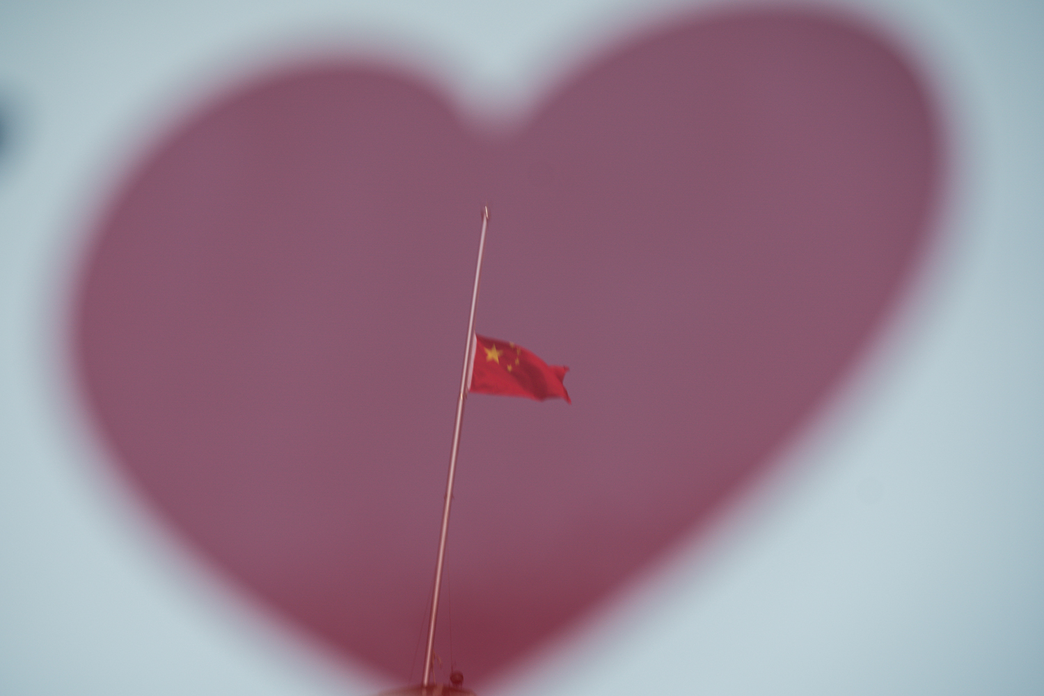 A reflector shows the Chinese national flag at half-staff in Shanghai on April 4 during a national day of mourning for victims of the pandemic.