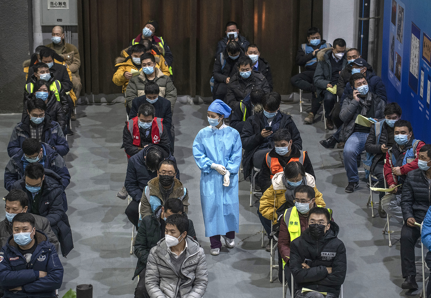 Chinese workers, including security guards, wait to receive a COVID-19 vaccine jab at a mass vaccination center for Chaoyang District in Beijing on Jan. 15.