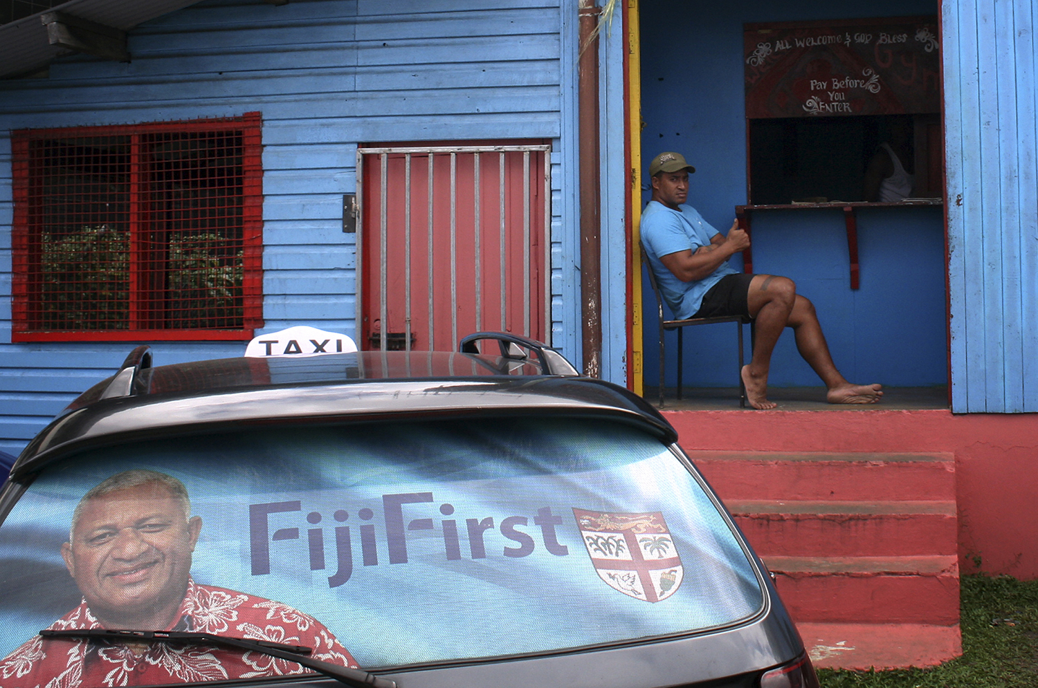 An election poster for Bainimarama in the rear window of a taxi as a man gestures from the doorway of a local gym in the Fiji capital of Suva on Aug. 26, 2014.
