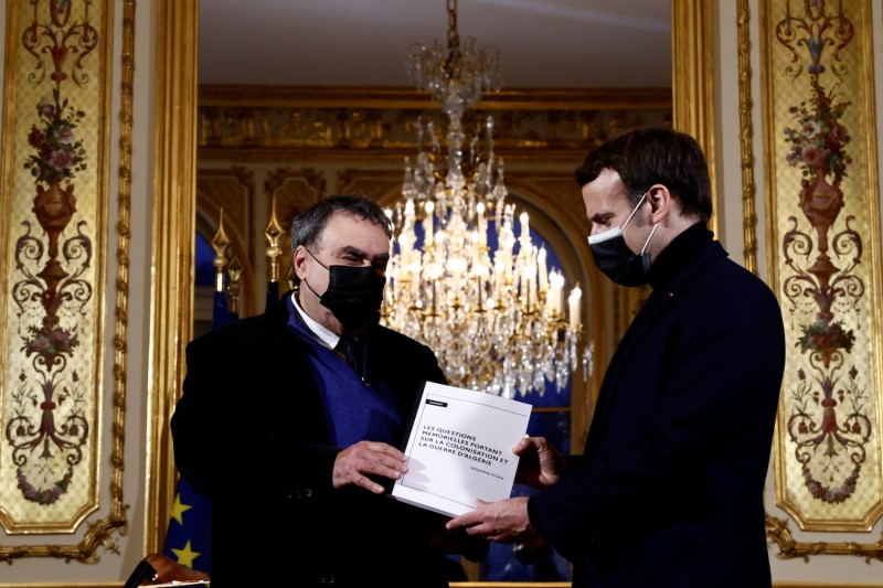French President Emmanuel Macron (R) poses with French historian Benjamin Stora for the delivery of a report on the colonization and the Algerian War in Paris on Jan. 20.