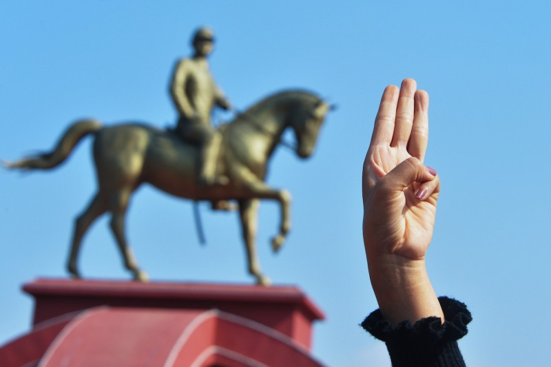 A protester holds up the three finger salute during a demonstration against the military coup at the monument of General Aung San, the late father of Suu Kyi in Naypyidaw on February 8, 2021.