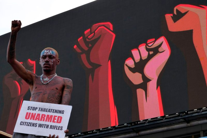 A protester gestures as he holds a placard at a live concert at the Lekki toll gate in Lagos, on October 15, 2020, during a demonstration to protest against police brutality and scrapping of Special Anti-Robbery Squad (SARS).