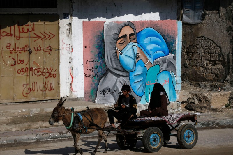 A Palestinian man and his wife ride a donkey cart past street art showing doctors wearing masks due to the COVID-19  pandemic in the Nuseirat refugee camp in Gaza Strip, on Nov. 16, 2020.