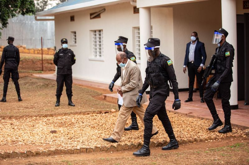 Paul Rusesabagina (C) is escorted by police officers at the Kicukiro Primary court in Kigali, Rwanda, on Sept.14, 2020.
