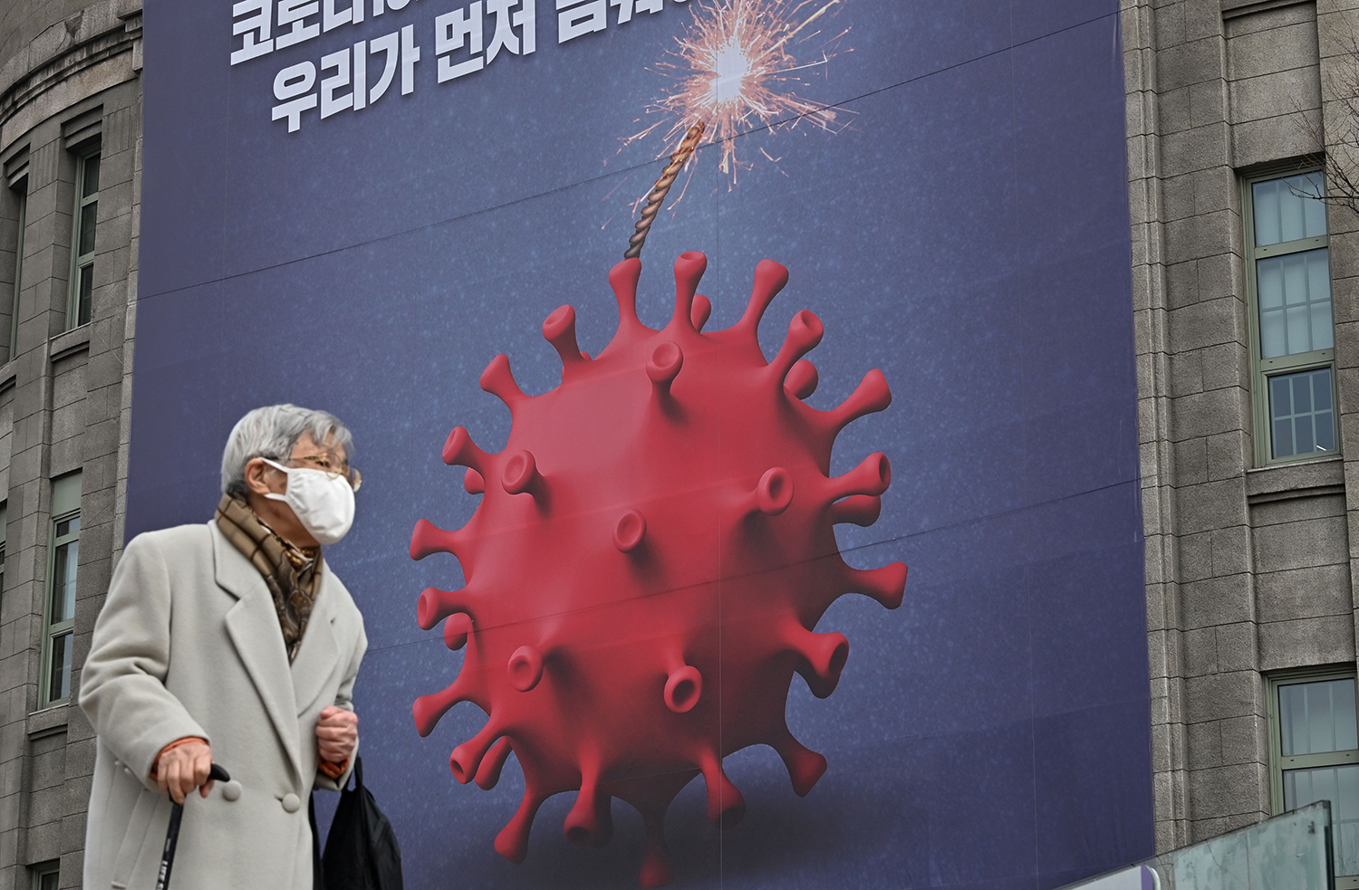 A woman walks past a poster depicting the coronavirus as a bomb at the City Hall in Seoul on Dec. 28, 2020.