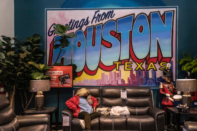 Marilu Alanis, 50, rests on a couch while taking shelter at Gallery Furniture store which opened its door and transformed into a warming station after winter weather caused electricity blackouts on February 18, 2021 in Houston.