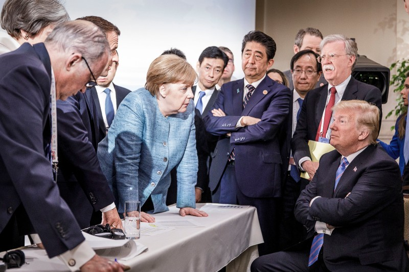 German Chancellor Angela Merkel deliberates with then-U.S. President Donald Trump at the G-7 summit Charlevoix, Canada, on June 9, 2018.