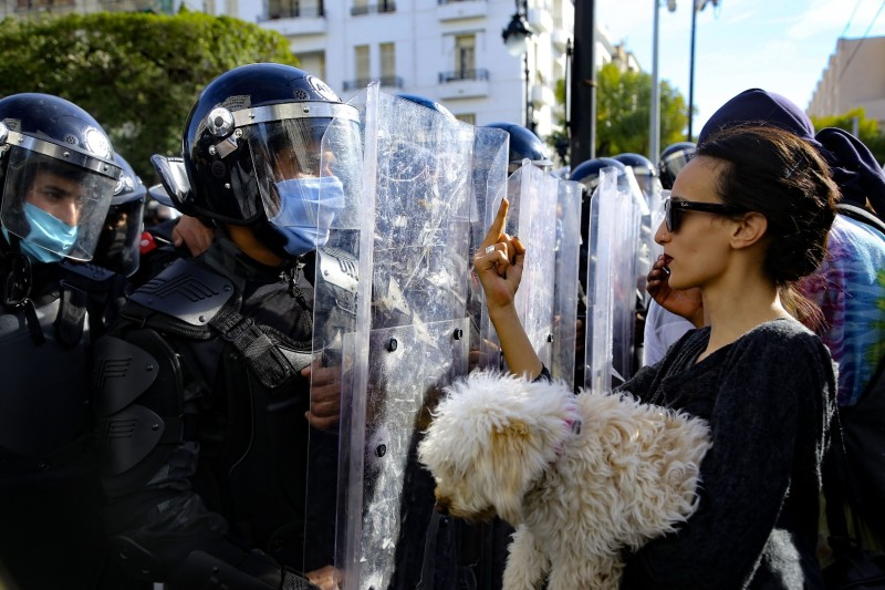 A Tunisian woman carrying a dog gestures with her middle finger at police officers during a demonstration in Tunis on Jan. 30.