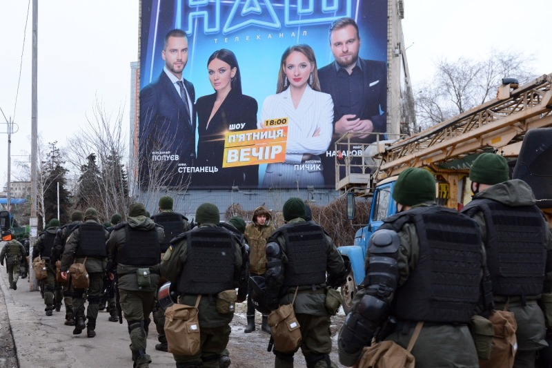Law enforcement officers patrol outside of the NASH TV channel headquarters during a demonstration in Kyiv, Ukraine, on Feb. 6. Protesters accused NASH TV of being pro-Kremlin and demanded it be taken off the air.