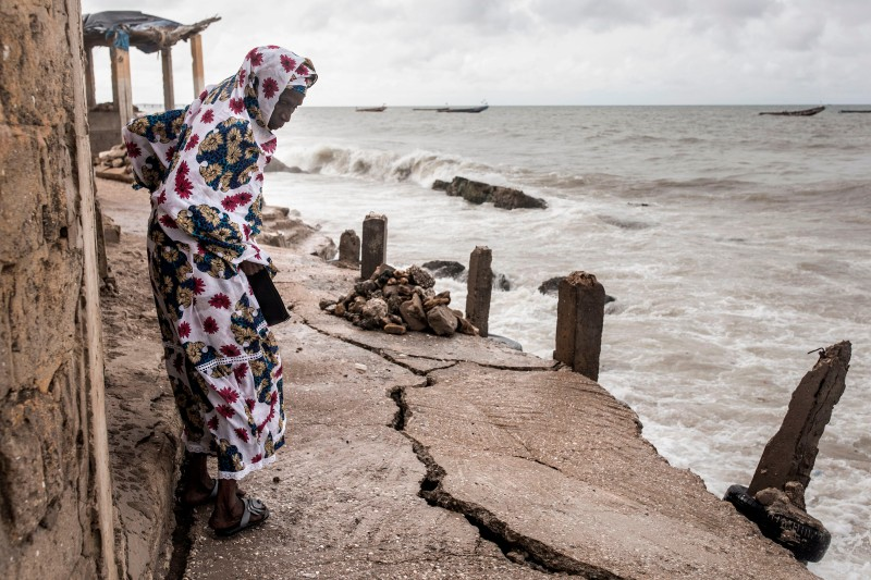 A woman looks at a newly formed crack in a walkway after a storm in Bargny, a fishing village in Senegal, on Sept. 18, 2020.