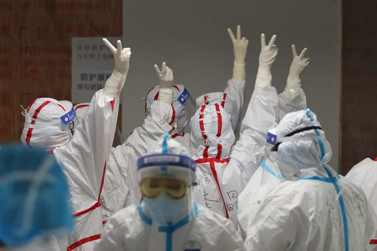 Medical staff cheer themselves up before going into an intesive care ward for COVID-19 patients at the Red Cross Hospital in Wuhan on March 16, 2020.