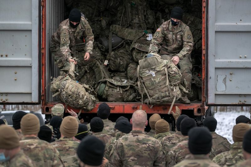 Soldiers unload bags at a U.S. base.