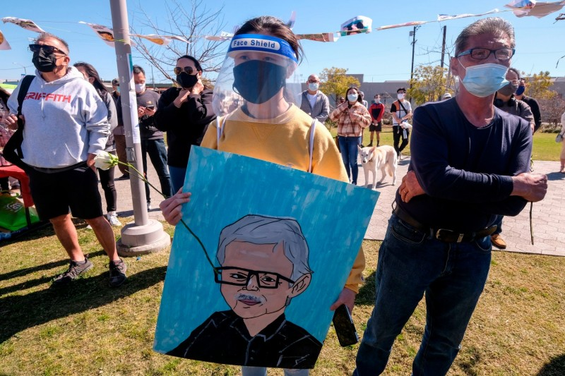 Protesters hold the image of a victim of racist attacks.