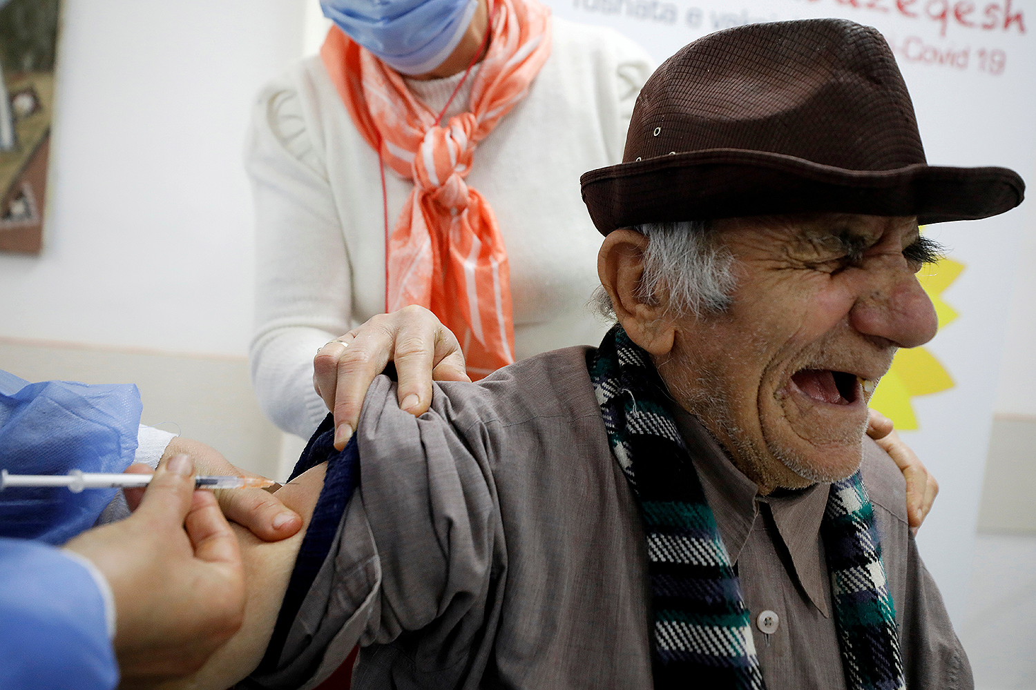 A health care worker administers a dose of the Pfizer-BioNTech COVID-19 vaccine to a man in Fier, Albania, on Feb. 19. Florion Goga/REUTERS