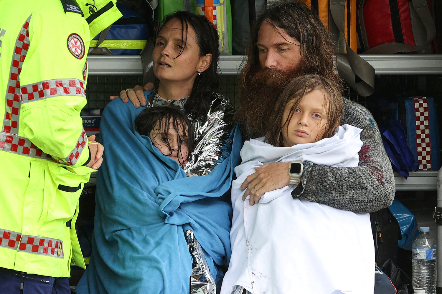 A family receives medical attention after the rescue boat that saved them from rising floodwaters capsized in Sydney on March 23. Loren Elliott/REUTERS