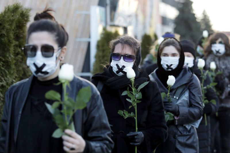 Masked women hold flowers during an anti-government protest in Belarus.