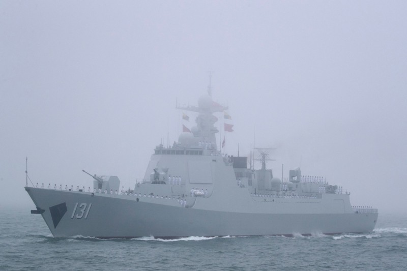 A Chinese ship at sea, visible through mist.