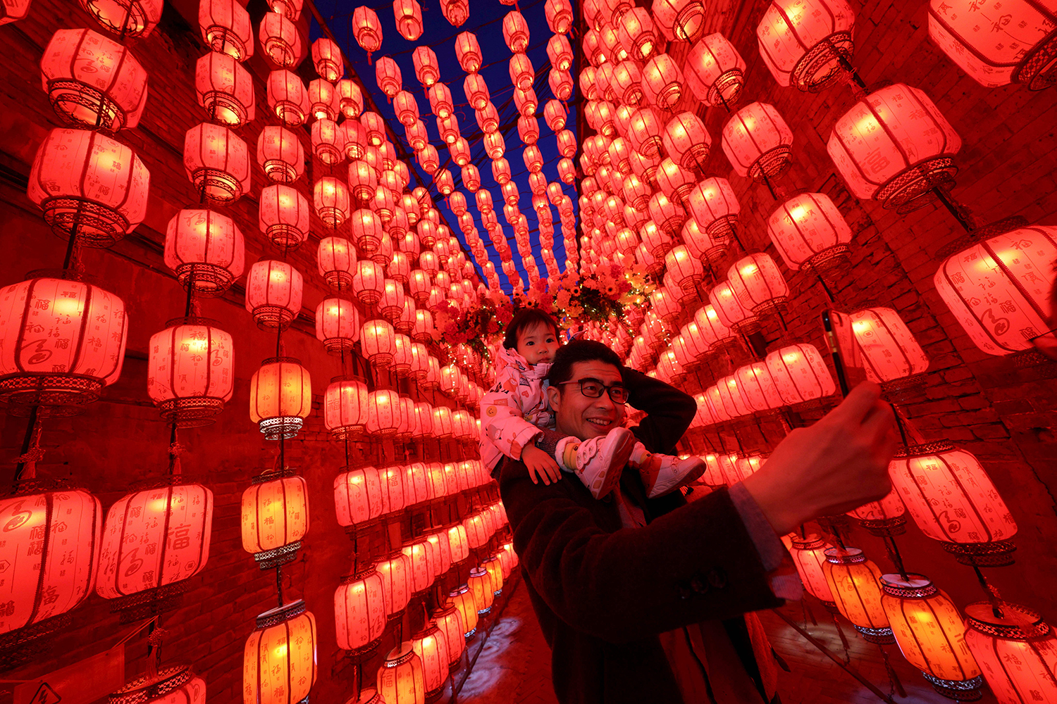 People take photos next to a display of lanterns during the Lantern Festival, marking the end of the Lunar New Year celebrations in Taiyuan, China, on Feb. 26. STR/AFP via Getty Images
